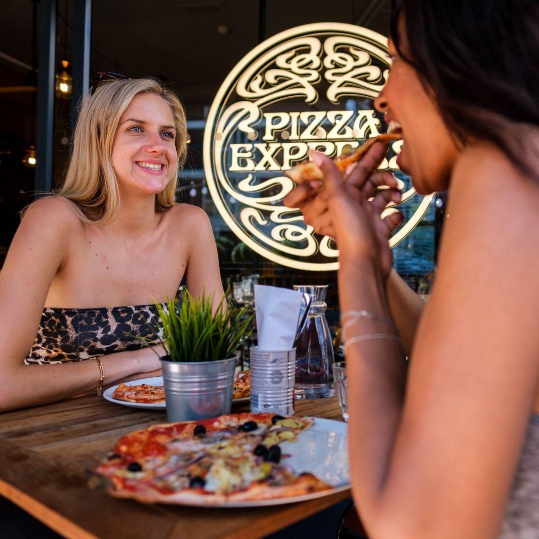 Customer eating pizza at Pizza Express